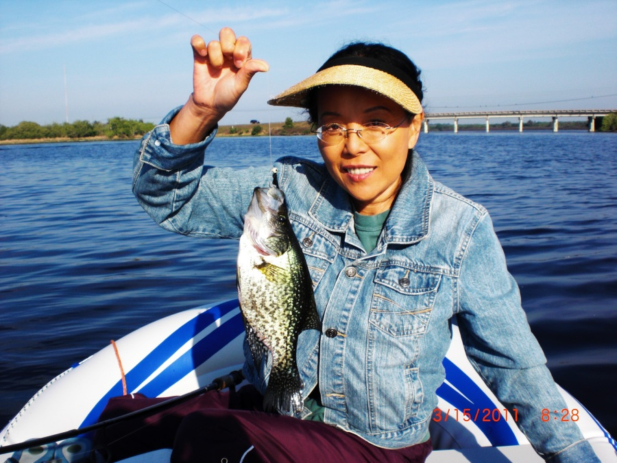 "Karen shows off the crappie (pronounced ""croppy"" she caught on Lake Manatee in their Sea Eagle. Timothy told us it was 10 inches then revised his report to 12 inches when Karen learned she'd been shortchanged. ""She always out-fishes me,"" says Timothy."