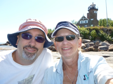 "David and Marge Back enjoy exploring Lake Superior. Their Sea Eagle 330 Sport Kayak is their ""full time transportation"" while their sailboat is at anchor. Other times, it's their ""exploration kayak"" as they kayak into sea caves. In the background is Lake Superior's Sand Island Lighthouse."