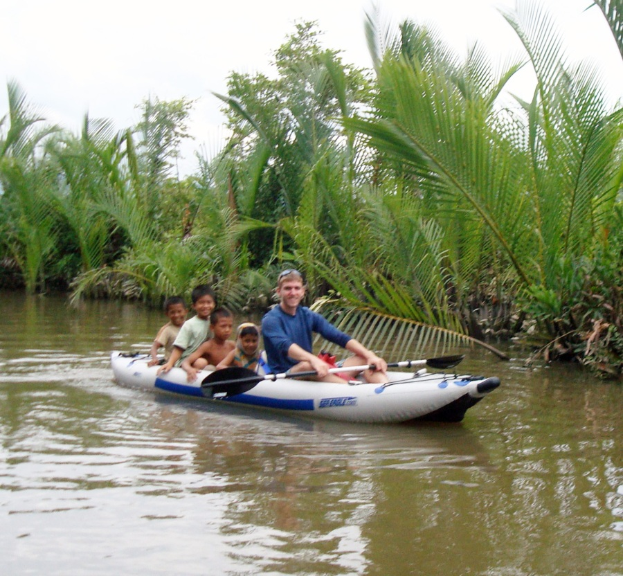 "Tim travels widely in Southeast Asia. Here, he's kayaking along the Kampot River in southern Cambodia. ""I gave a few kids a ride along the way,"" he says."