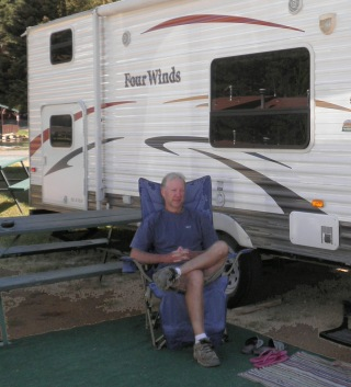 Mike takes some time out beside their RV. There are two bunk beds where the two windows are. Below the bottom bunk is a storage compartment where they store their Sea Eagles.